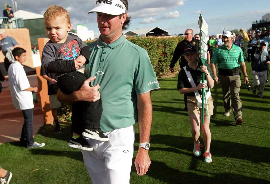 Phoenix Open leader Bubba Watson has his hands full with son Caleb after finishing his round Saturday. Photo: David Wallace, MBO / The Arizona Republic
