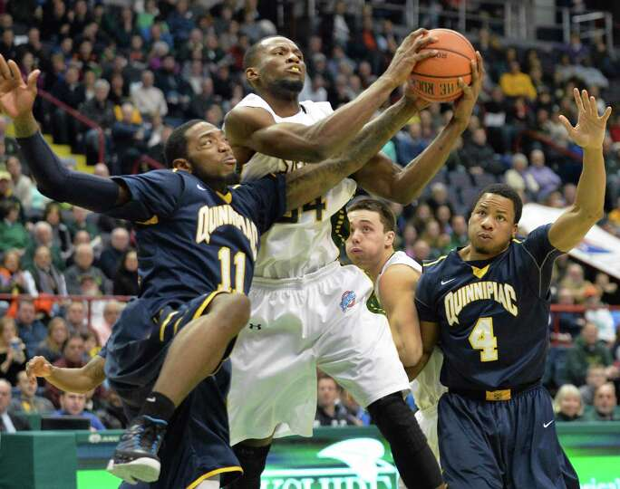 Siena's # 34 Imoh Silas, center, Quinnipiac's #11 Al Sumbry, left, tangle during Saturday's game at
