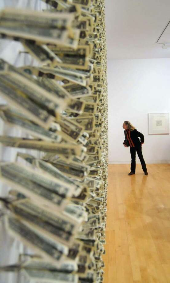 "The Aldrich Museum in Ridgefield, CT. had an openinng of Five new exhibits on Sunday, Jan. 31, 2010. Lisa Mann of Ridgefield takes a look at one of Tom Molloy's exhibits called ""Swarm, 2006"". The piece consists of 3600 folded US dollar bills piercing the wall. Photo: Lisa Weir / The News-Times"