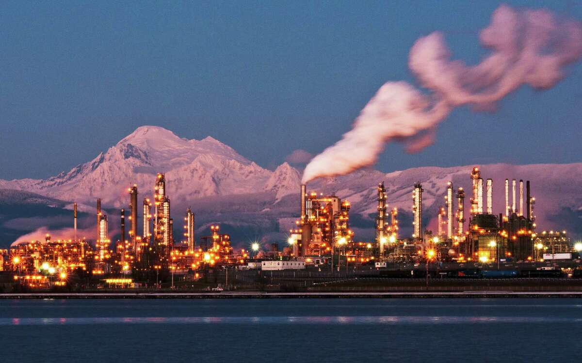 Washington state's Mount Baker is illuminated by the setting sun as the lights come on at the Tesoro refinery in Anacortes, site of the disaster in 2010.