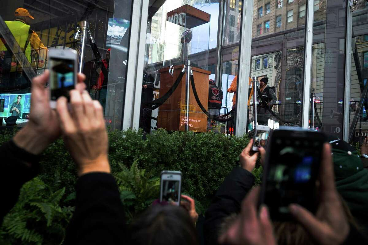 Onlookers photograph the Vince Lombardi trophy Saturday, Feb. 1, 2014, in New York City.