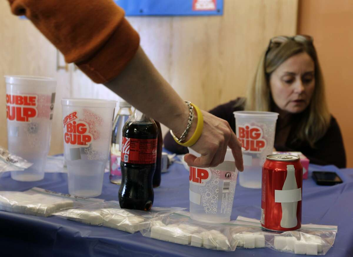 Volunteers arrange a display showing the sugar content in soda drinks before a rally to launch a campaign to tax sugar-sweetened beverages in San Francisco. Supervisors Scott Wiener and Eric Mar combined their two competing measures to create a unified effort that would charge a 2-cents-per-ounce sugary drink tax.