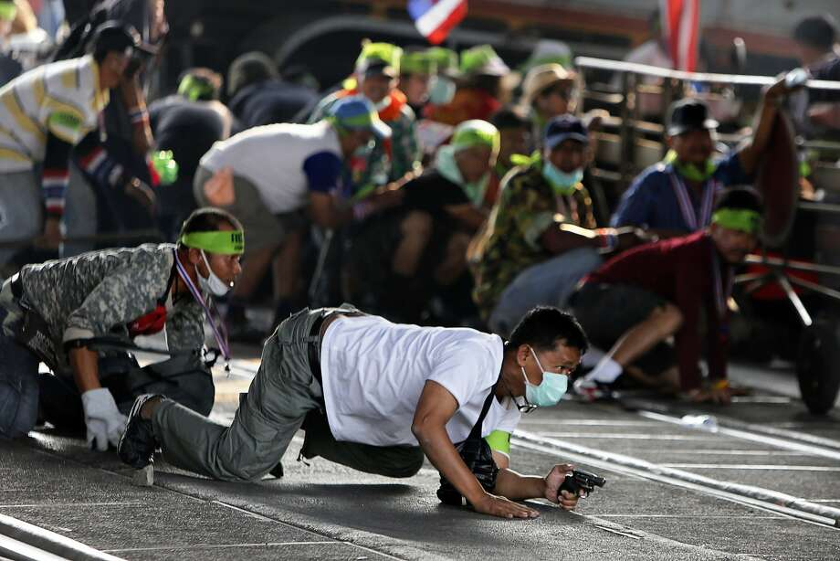 A government protester crawls with his gun during a battle between supporters and opponents of Thailand's leadership in Bangkok. Photo: Nir Elias, Reuters