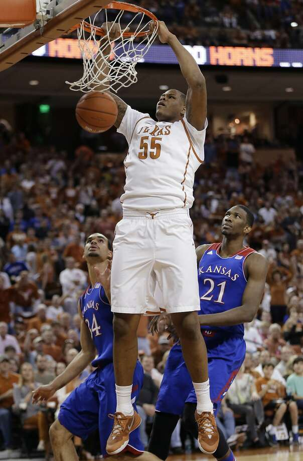 Texas' Cameron Ridley (55) scores over Kansas' Perry Ellis (34) and Joel Embiid (21) during the first half of an NCAA college basketball game, Saturday,  Feb. 1, 2014, in Austin, Texas. (AP Photo/Eric Gay) Photo: Eric Gay, Associated Press