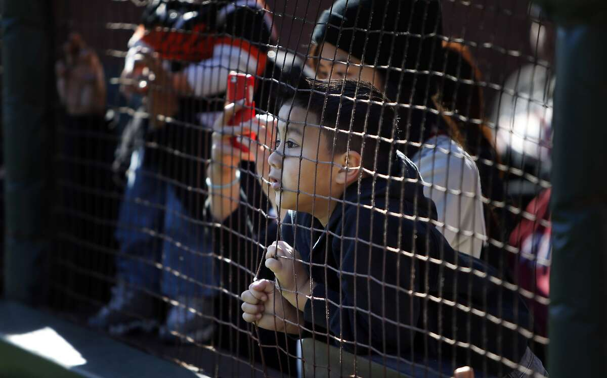 Jordan Escobar, 6, of Hercules, peeks through the netting as Sergio Romo speaks with Brian Murphy and Paul Macaffrey on the KNBR stage on Saturday. San Francisco Giants fans were treated to a day with their favorite players during Fanfest at AT&T Park in San Francisco, Calif., on Saturday, February 1, 2014.