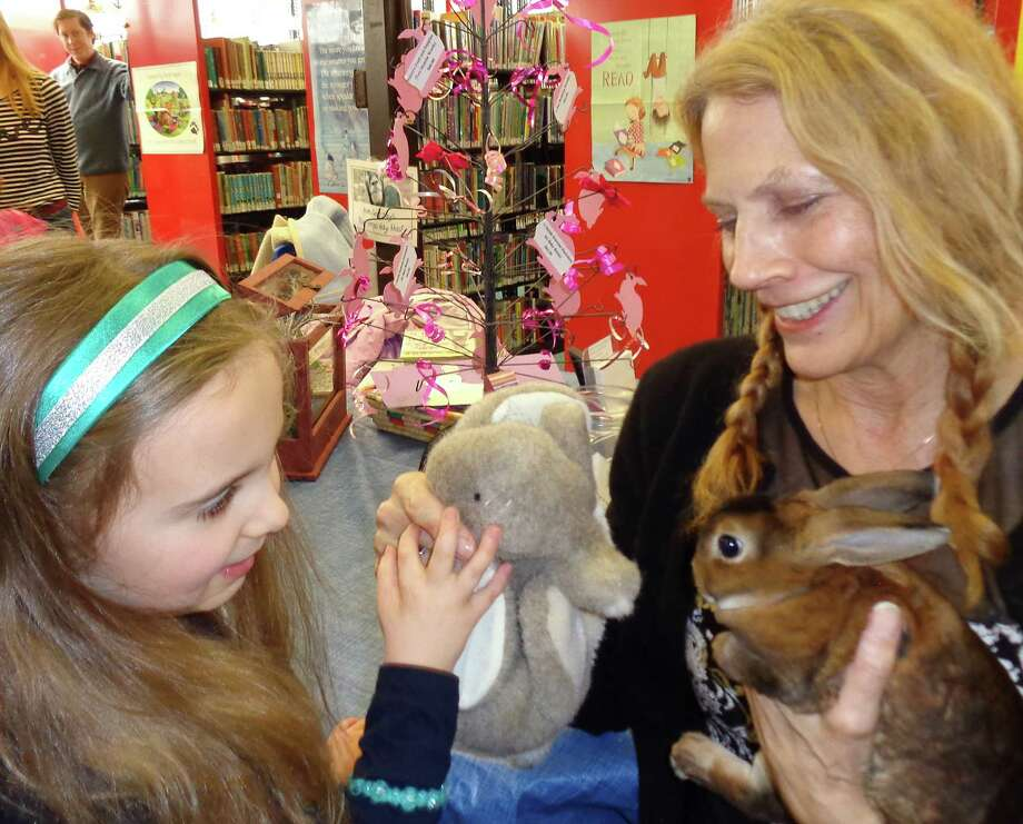 Pequot Library Children's Librarian Susan Ei introduces the library's new rabbit to Allison Cancro, 7, on Saturday as Allison introduces the animal to a stuffed rabbit puppet. Photo: Meg Barone / Fairfield Citizen contributed