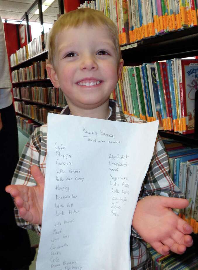 Harlan Lewandowski, 4, of Fairfield, shows the list of 27 names he and his sister Anna, 2 1/2, came suggested as possible names for the Pequot Library's new bunny. Among their suggestions were Cookies, Marshmallow, Cinderella, Cotton Ball, Sweet Apple and Little Pizza. Photo: Meg Barone / Fairfield Citizen contributed