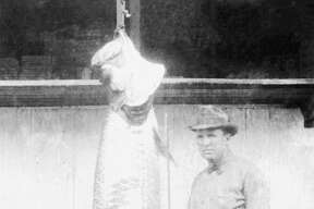 An angler stands next to his catch, a 7 foot long tarpon caught near Palacios, Texas on September 3, 1923.