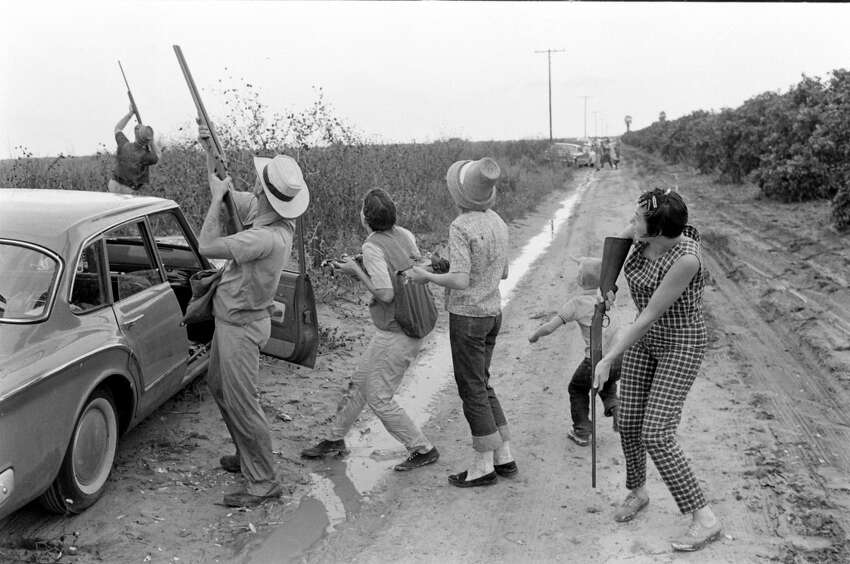 Members of the Thrash and Burns families, and their friends hunt white-winged doves along a muddy, dirt road, Giddings, Texas, 1961.