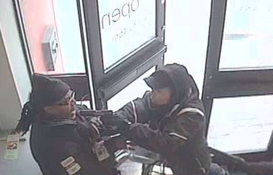 In an image from a security camera provided by the FBI, a robbery suspect, right, points a handgun at an armored truck guard at an HSC Bank branch in the Queens borough of New York, Friday, Jan. 31, 2014. Federal investigators are searching for three men they say held up an armored truck guard at the Queens bank in broad daylight. They say the guard was sprayed with a chemical after making a regularly scheduled pickup at the bank. Authorities say the men fled in a blue or black Ford Explorer. Armored truck company GardaWorld has offered a $50,000 reward for information leading to an arrest and conviction in the case. Photo: AP  / FBI the FBI