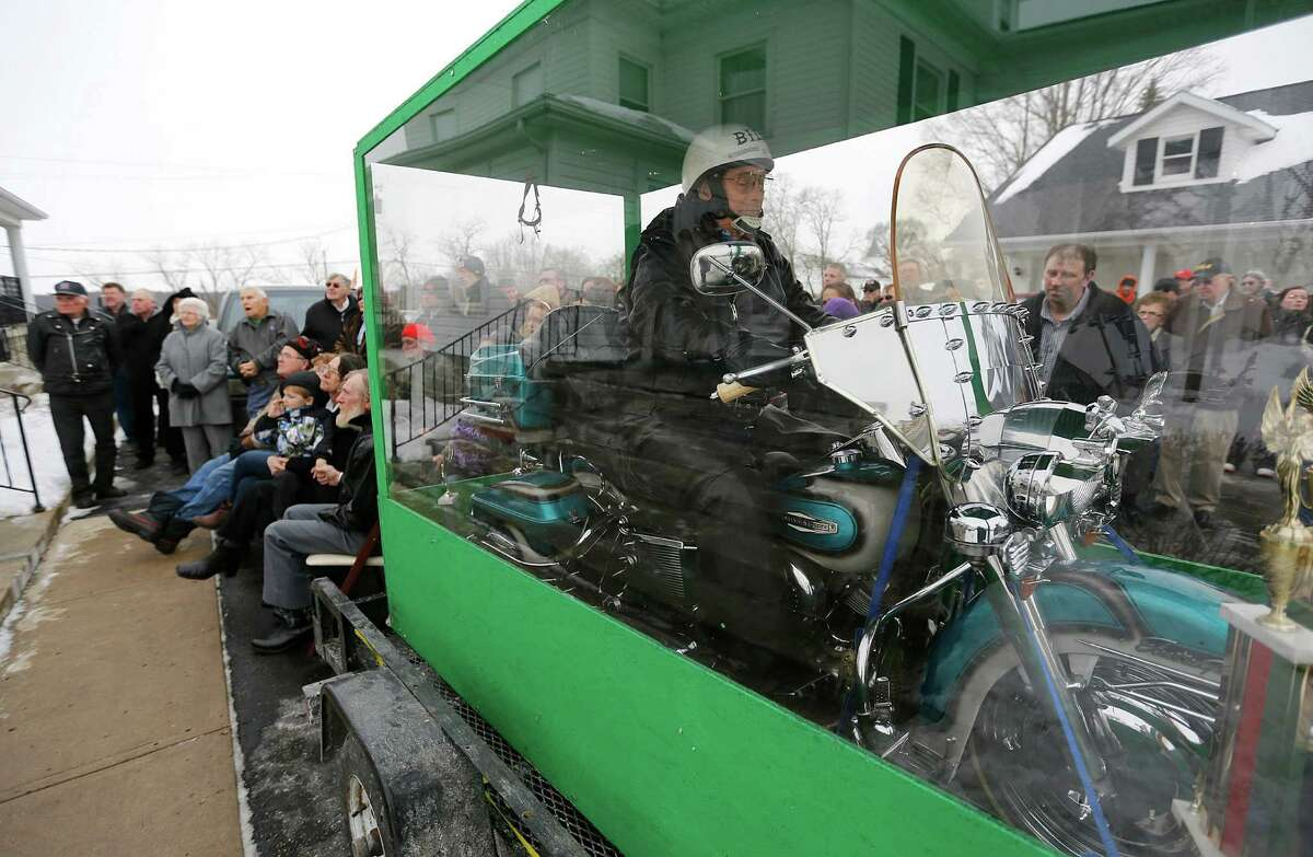 The body of Bill Standley secured to his 1967 Harley Davidson rests inside a plexiglass box during his funeral service in Mechanicsburg, Ohio on Friday, Jan. 31, 2014. Standley's family said he'd been talking about it for years and liked to take people to the garage to show off the unusual casket his two sons had built for him. He told people he didn't just want to ride off to heaven, he wanted the world to see him do it in the big see-through box.