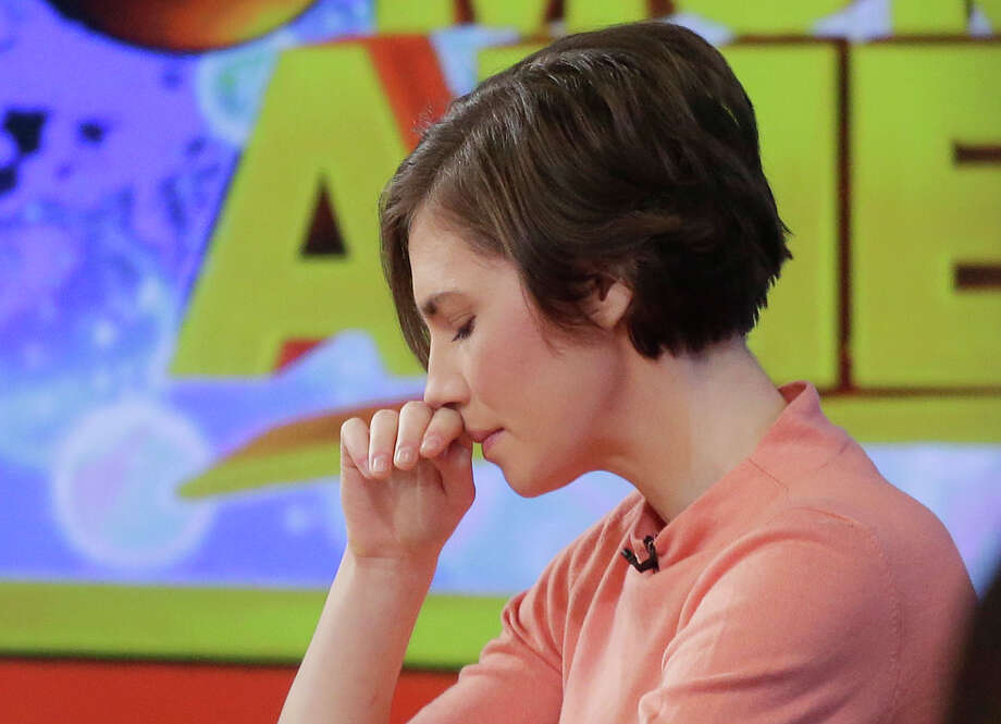 "Amanda Knox puts her hand to her face while making a television appearance, Friday, Jan. 31, 2014 in New York. Knox said she will fight the reinstated guilty verdict against her and an ex-boyfriend in the 2007 slaying of a British roommate in Italy and vowed to ""never go willingly"" to face her fate in that country's judicial system . ""I'm going to fight this to the very end,"" she said in an interview with Robin Roberts on ABC's ""Good Morning America."" Photo: Mark Lennihan, AP  / AP2014"