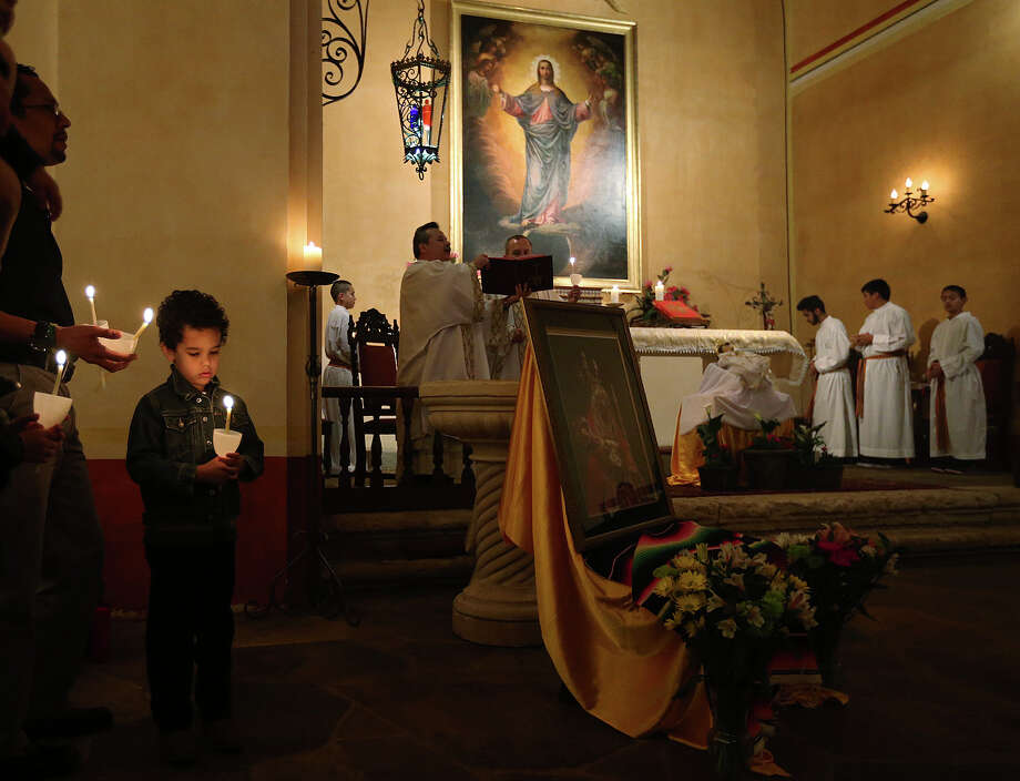 Inti (cq), Zapata, 5, and his father, Jaime Zapata, left, hold lighted candles as faithful celebrate La Candelaria during Mass at Mission Concepcion, Sunday, Feb. 2, 2014. La Candelaria celebrates the Presentation of the Baby Jesus in the Temple 40 days after his birth. Father David Garcia held four blessing during and after the service that included, the Baby Jesus, newborn children, candles and the blessing of the throat. Photo: JERRY LARA, San Antonio Express-News / © 2014 San Antonio Express-News