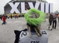 Seattle Seahawks fan Shirley Wolff, of Puyallup, Wash., takes a photo outside MetLife Stadium before the NFL Super Bowl XLVIII football game between the Seattle Seahawks and the Denver Broncos, Sunday, Feb. 2, 2014, in East Rutherford, N.J. (AP Photo/Charlie Riedel)