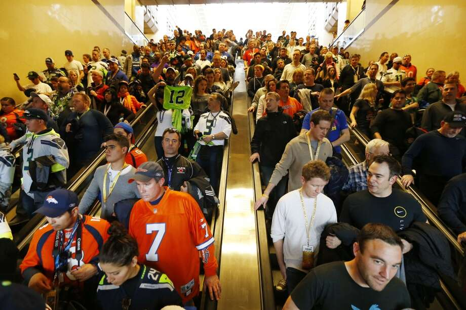Football fans make their way to trains on Sunday, Feb. 2, 2014, in Secaucus, N.J. The Seattle Seahawks are scheduled to play the Denver Broncos in NFL football's Super Bowl XLVIII game on Sunday evening at MetLife Stadium in East Rutherford, N.J. (AP Photo/Matt Rourke) Photo: AP