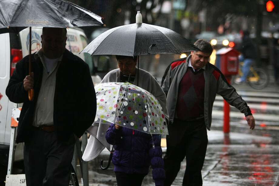People covering from the rain with umbrellas, walk quickly down 24th Street in the Mission District of San Francisco, Calif. on Feb. 2, 2014. Photo: Deborah Svoboda, The Chronicle