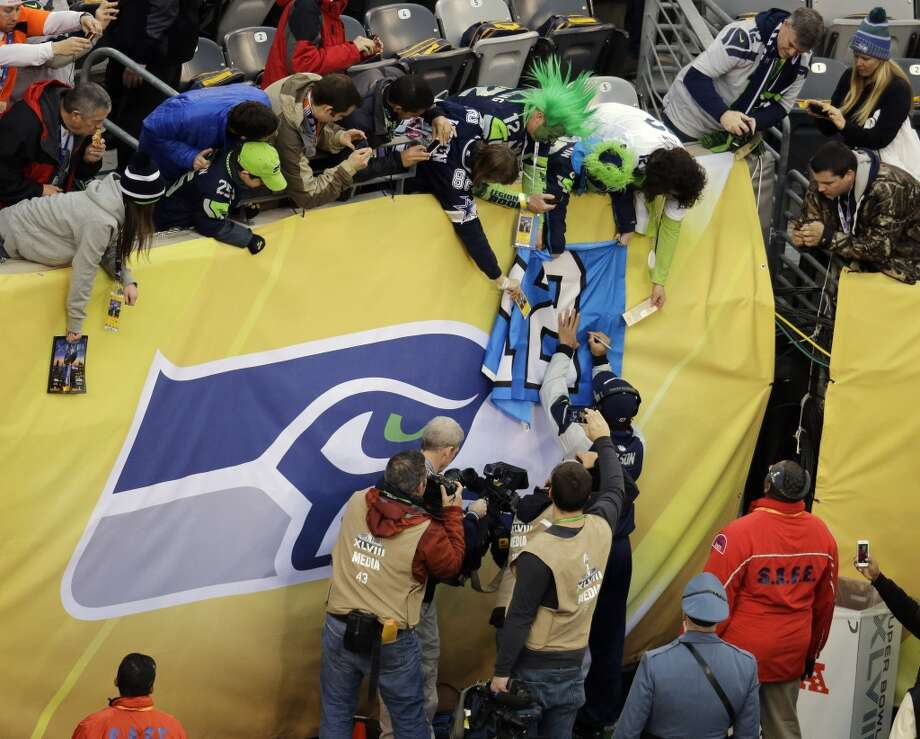 Seattle Seahawks' Russell Wilson signs a jersey denoting the 12 player, before the NFL Super Bowl XLVIII football game against the Denver Broncos, Sunday, Feb. 2, 2014, in East Rutherford, N.J. (AP Photo/Mel Evans) Photo: AP