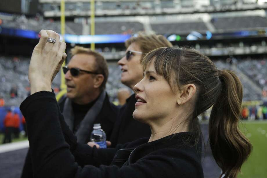 Actress Jennifer Garner takes a photo as actors Kevin Costner, left, and Denis Leary look on, at MetLife Stadium before the NFL Super Bowl XLVIII football game between the Seattle Seahawks and the Denver Broncos Sunday, Feb. 2, 2014, in East Rutherford, N.J. (AP Photo/Matt Slocum) Photo: Matt Slocum, AP