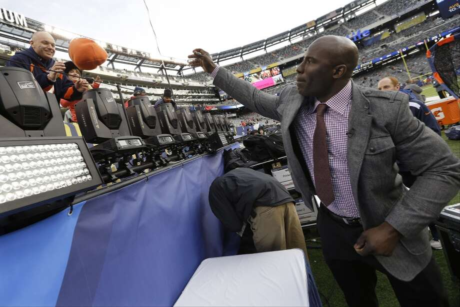 Former Denver Bronco Terrill Davis tosses an autographed hat to a fan before the NFL Super Bowl XLVIII football game Sunday, Feb. 2, 2014, at MetLife Stadium in East Rutherford, N.J. (AP Photo/Mark Humphrey) Photo: Mark Humphrey, AP