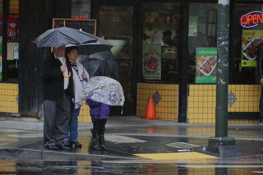 People take shelter under umbrellas while waiting at a corner on 24th Street in the Mission District of San Francisco, Calif. on Feb. 2, 2014. Photo: Deborah Svoboda, The Chronicle