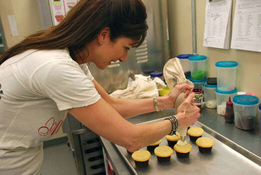 Terese Yates, owner of Frost Bake Shoppe, decorates cupcakes. Yates competed on the Food Network's 'Cupcake Wars.' Photo: Lindsay Peyton