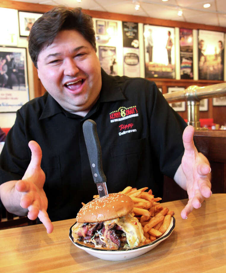Ziggy Gruber shows off one of the burgers. The Galleria-area deli Kenny & Ziggy's was featured on Food Network's 'Diners, Drive-Ins and Dives.' Photo: Courtesy Photo, Kenny & Ziggy's