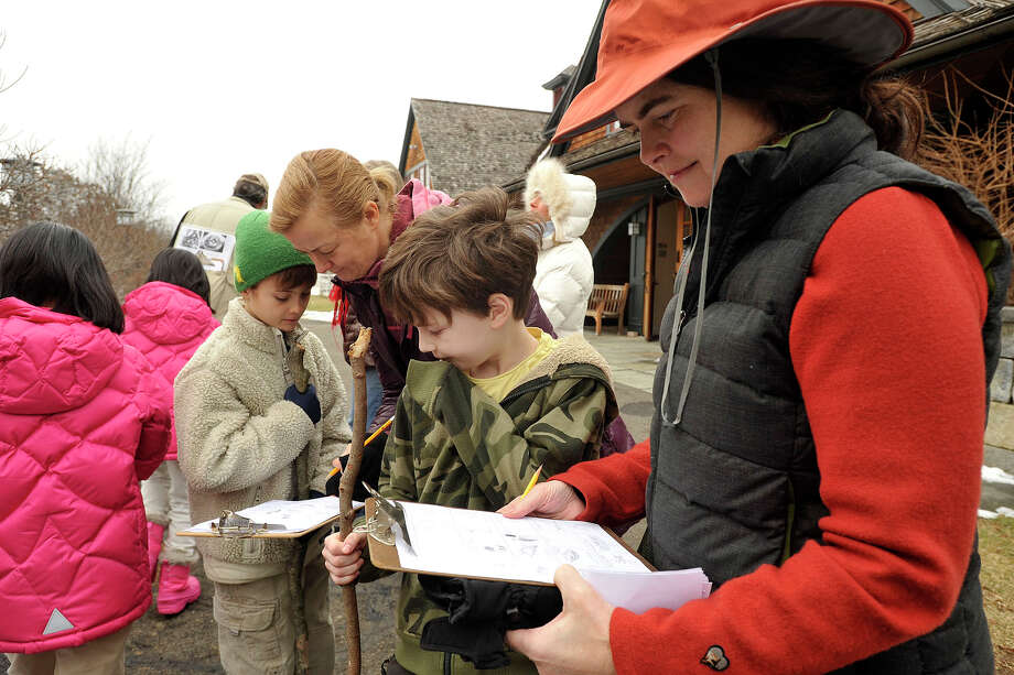 Viva Hardigg, right, and her son Henry Carter as well as Liesbeth Carballo and her son, Lucas, keep notes on what insects they find during the Insects in Winter Walk at the Audubon Center in Greenwich, Conn., on Sunday, Feb. 2, 2014. Photo: Jason Rearick / Stamford Advocate