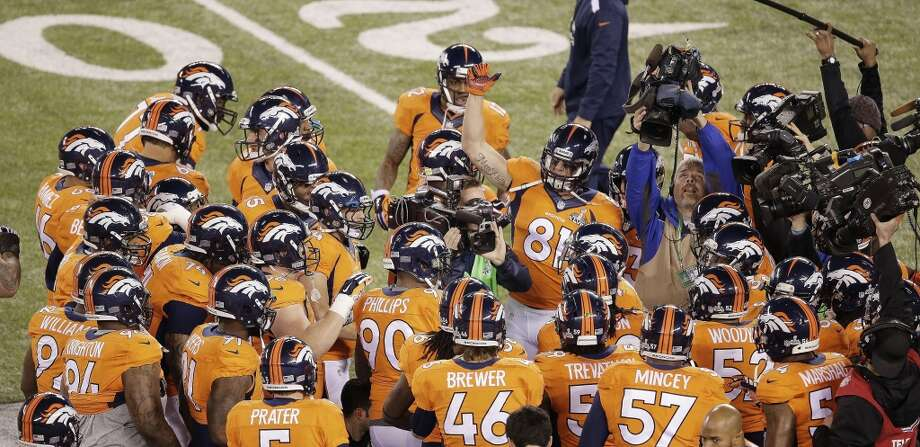 Broncos players gather before the start of the Super Bowl. Photo: Charlie Riedel, Associated Press