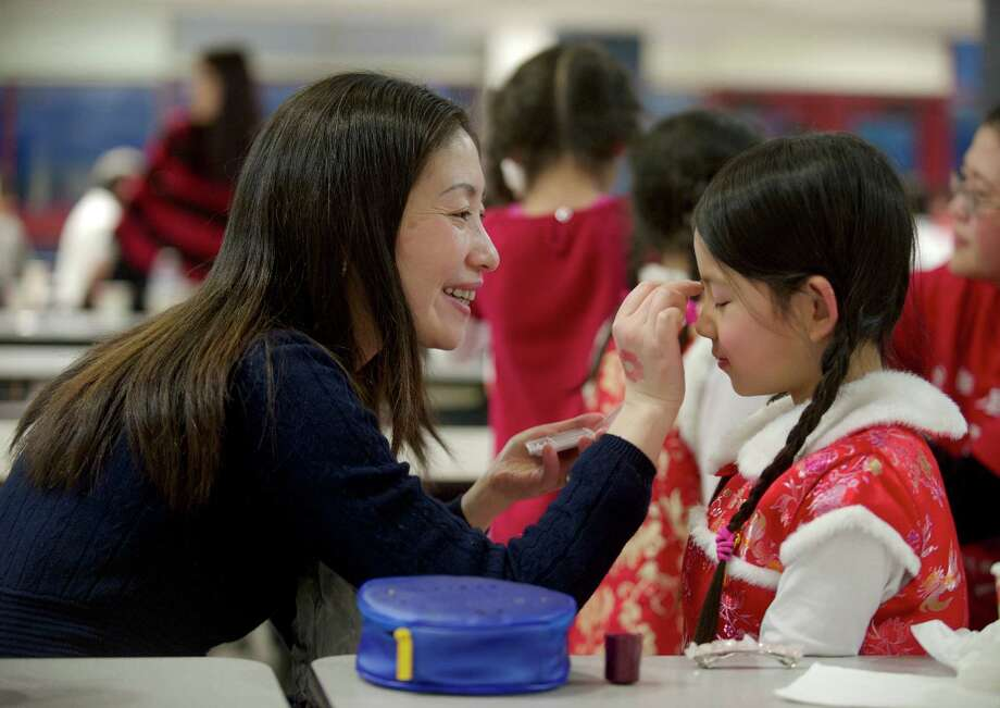 Rachel Tang, of Brookfield, applies makeup to Sarah Seo, 8, of New Milford, before Sarah takes part in the nights stage performance during the Western Connecticut Chinese Association's 2014 Chinese New Year celebration party, held at Newtown High School, Newtown, Conn, on Sunday, February 2, 2014. Photo: H John Voorhees III / The News-Times Freelance