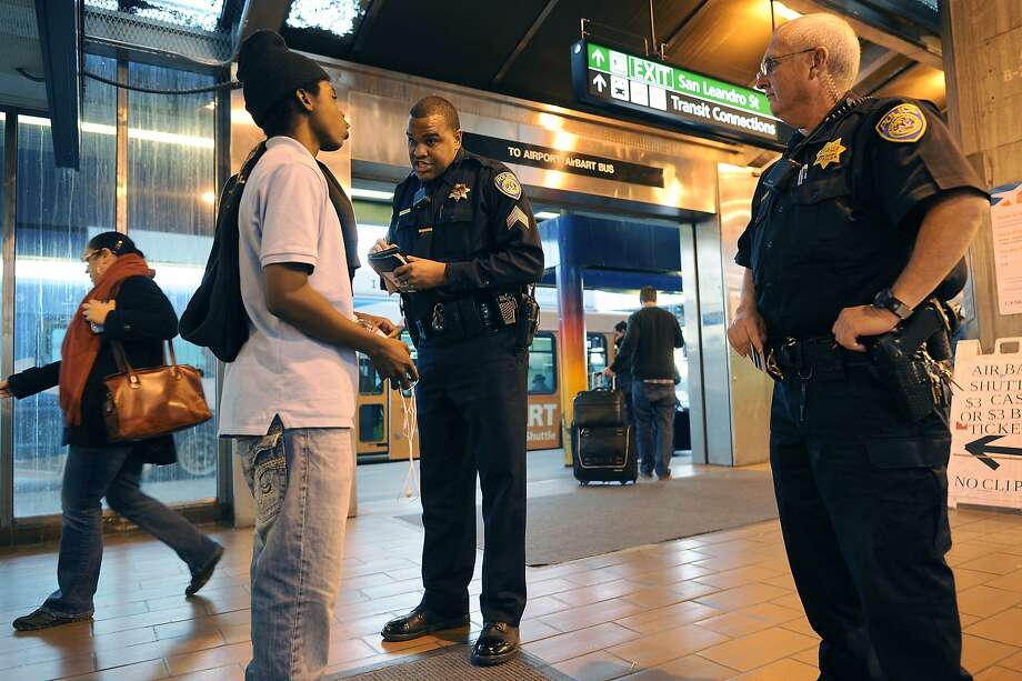 BART police Sgt. Jason Scott, backed up by Officer Kory Frost, talks to a young man detained for alleged fare evasion at the Coliseum BART Station in Oakland. BART officers are armed to protect the public. Photo: Michael Short, Special To The Chronicle
