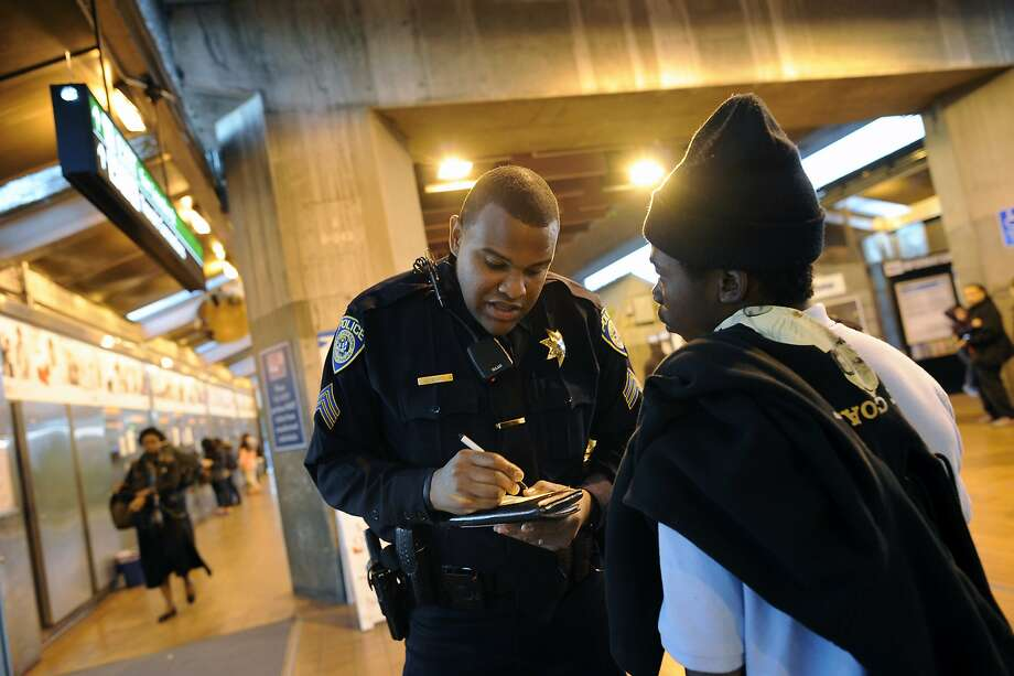 BART police Sgt. Jason Scott writes down personal information given by a young man that he detained for fare evasion at the Coliseum BART station in Oakland, CA, in this file photo from January 31, 2014.New California legislation ends criminal penalties for transit fare evasion by those under 18. Photo: Michael Short, Special To The Chronicle