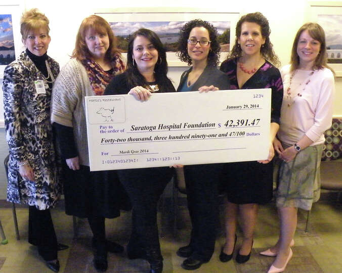 Beth Alexander, co-owner of Hattie's, presents Saratoga Hospital Foundation members with a check for