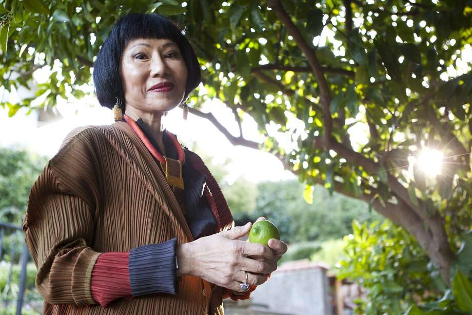 "Amy Tan. The international best-selling author who penned ""The Joy Luck Club "" was born in Oakland. Pictured: Tan picks limes from a tree in her yard as she poses for portraits at her home in Sausalito on Tuesday, October 29, 2013. Photo: Michael Short, The Chronicle"