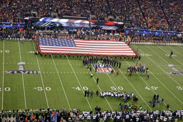 Image of the American flag on a football field.