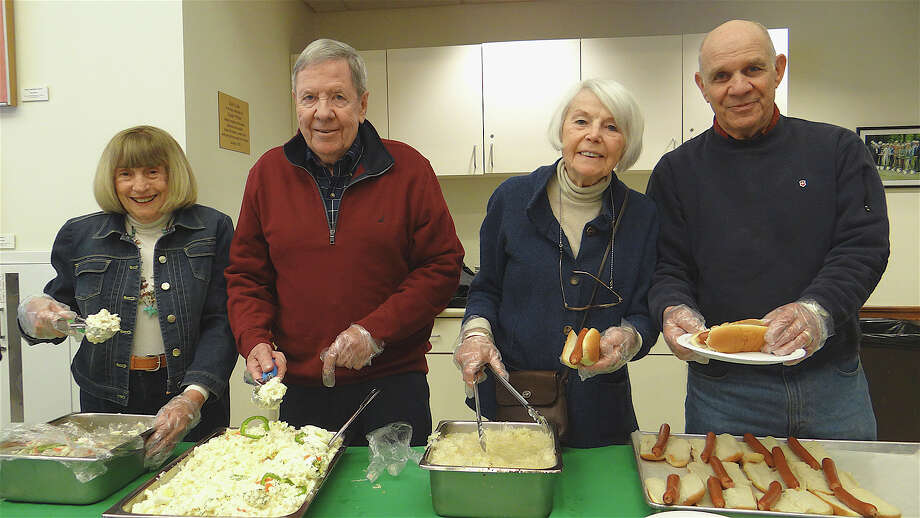 "Dishing out the ""dogs"" at Sunday's Super Bowl tailgate event at the Westport Center for Senior Activities were, from left: Jo Luscombe, John Thompson, Jean McGurk and Al Landis. Photo: Mike Lauterborn / Westport News"