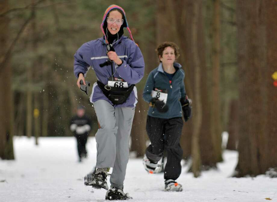 Racers, Beth Trapasso, left, from Wilton and Peggy McKeown from Moreau, run towards the finish line during the Saratoga Winterfest 5k Snowshoe Race at Saratoga Spa State Park on Sunday, Feb. 2, 2014 in Saratoga Springs, NY.  The race is part of the Dion snowshoe series.   (Paul Buckowski / Times Union) Photo: Paul Buckowski / 10025575A