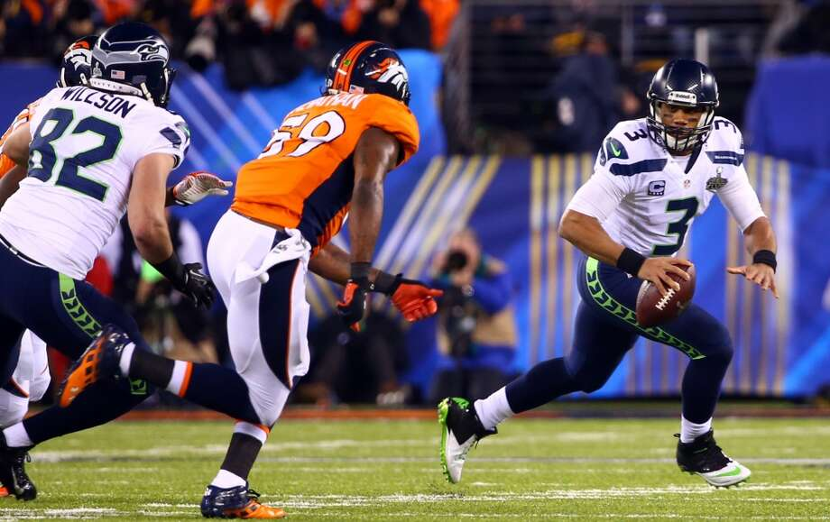 Seattle's Russell Wilson, right, scrambles, while pursued by Denver's Danny Trevathan, left, at Super Bowl XLVIII Sunday, Feb. 2, 2014, at MetLife Stadium in New Jersey. (Joshua Trujillo, seattlepi.com) Photo: JOSHUA TRUJILLO, SEATTLEPI.COM