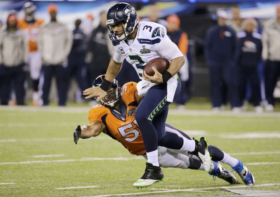Seattle Seahawks quarterback Russell Wilson (3) breaks a tackle by Denver Broncos middle linebacker Paris Lenon during the third quarter  in the NFL Super Bowl XLVIII football game in East Rutherford, New Jersey, February 2, 2014. (REUTERS/Ray Stubblebine) Photo: RAY STUBBLEBINE, Reuters