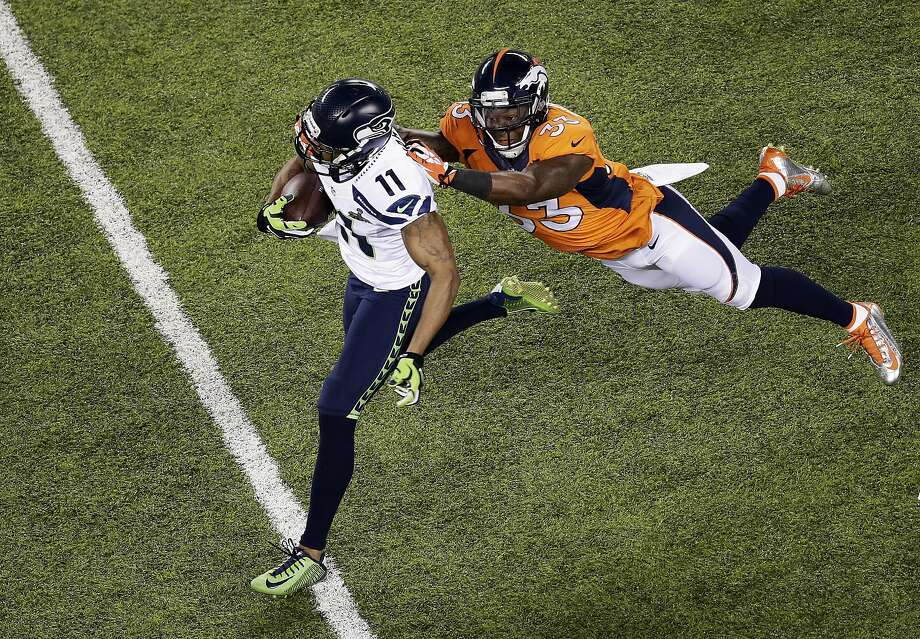 EAST RUTHERFORD, NJ - FEBRUARY 02: Wide receiver Percy Harvin #11 of the Seattle Seahawks runs with the ball while being tackled by strong safety Duke Ihenacho #33 of the Denver Broncos during Super Bowl XLVIII at MetLife Stadium on February 2, 2014 in East Rutherford, New Jersey.  (Photo by Win McNamee/Getty Images) Photo: Win McNamee, Getty Images