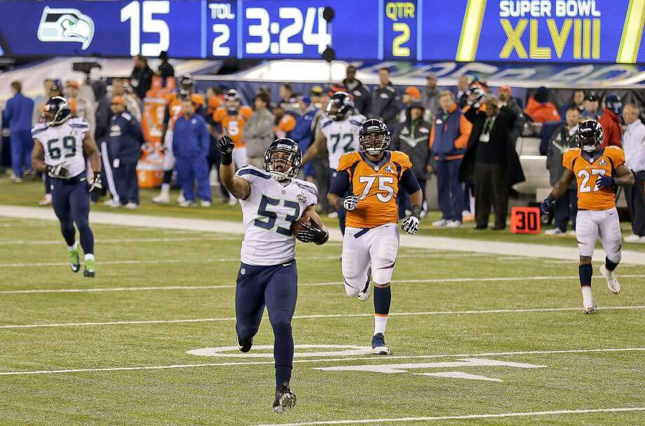 Seattle linebacker Malcolm Smith scores on a 69-yard return of an interception thrown by Peyton Manning, below, making the score 22-0 in the second quarter. Photo: Gregory Bull, Associated Press