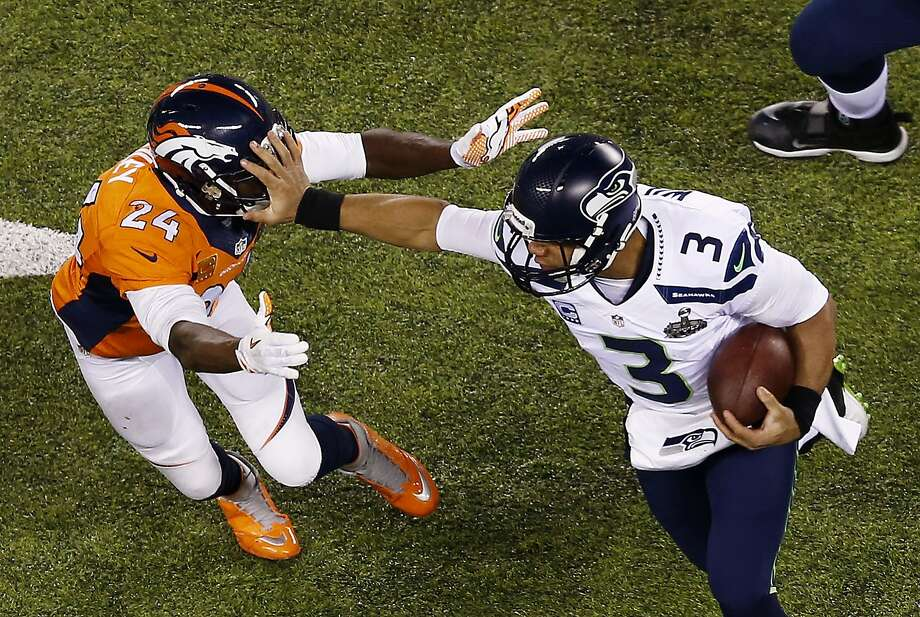 Quarterback Russell Wilson #3 of the Seattle Seahawks stiff arms cornerback Champ Bailey #24 of the Denver Broncos  during Super Bowl XLVIII at MetLife Stadium on February 2, 2014 in East Rutherford, New Jersey.  Photo: Jeff Zelevansky, Getty Images