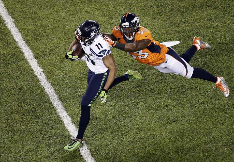 Wide receiver Percy Harvin #11 of the Seattle Seahawks runs with the ball while being tackled by strong safety Duke Ihenacho #33 of the Denver Broncos during Super Bowl XLVIII at MetLife Stadium on February 2, 2014 in East Rutherford, New Jersey.  (Photo by Win McNamee/Getty Images) Photo: Win McNamee, Getty Images