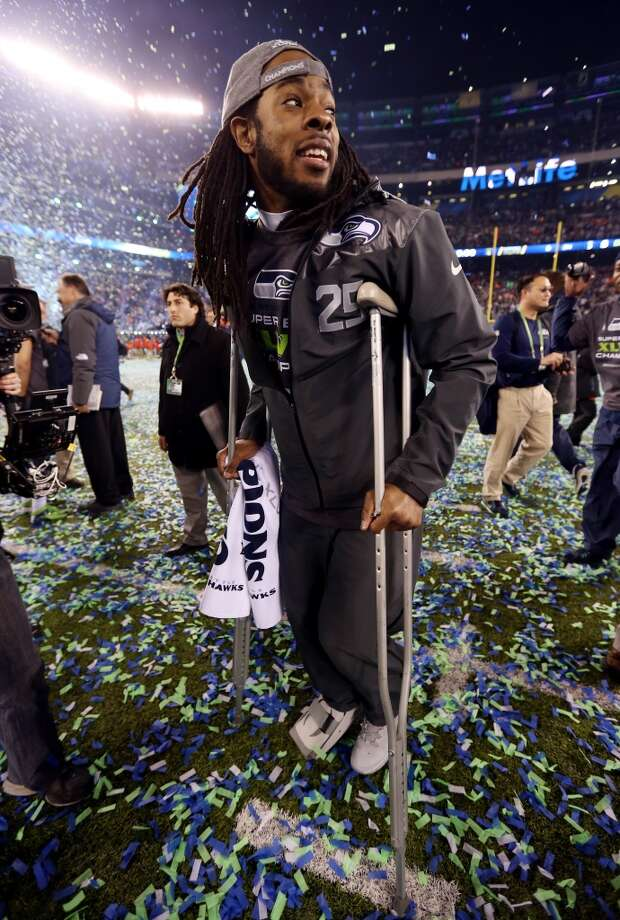 Cornerback Richard Sherman #25 of the Seattle Seahawks uses crutches as he walks across the field in celebration of their 43-8 victory over the Denver Broncos during Super Bowl XLVIII at MetLife Stadium on February 2, 2014 in East Rutherford, New Jersey.  (Photo by Jeff Gross/Getty Images) Photo: Jeff Gross, Getty Images