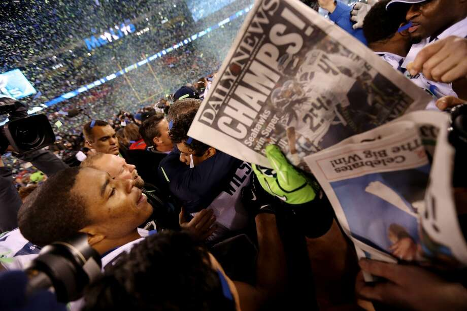 Media surround quarterback Russell Wilson #3 of the Seattle Seahawks after their 43-8 victory over the Denver Broncos during Super Bowl XLVIII at MetLife Stadium on February 2, 2014 in East Rutherford, New Jersey.  (Photo by Jeff Gross/Getty Images) Photo: Jeff Gross, Getty Images