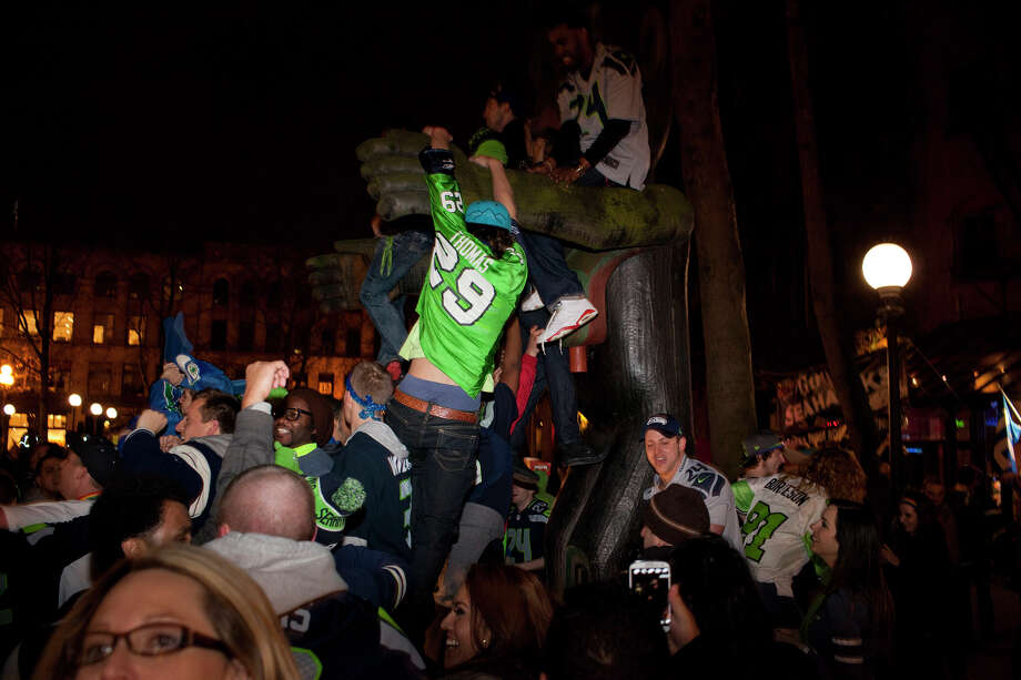 Fans climb on a sculpture at Occidental Park in Pioneer Square after the Seattle Seahawks' 43-8 win against the Denver Broncos in Super Bowl XLVIII Sunday in Seattle. Photo: CHRIS WILSON, (Chris Wilson,  Seattlepi.com)