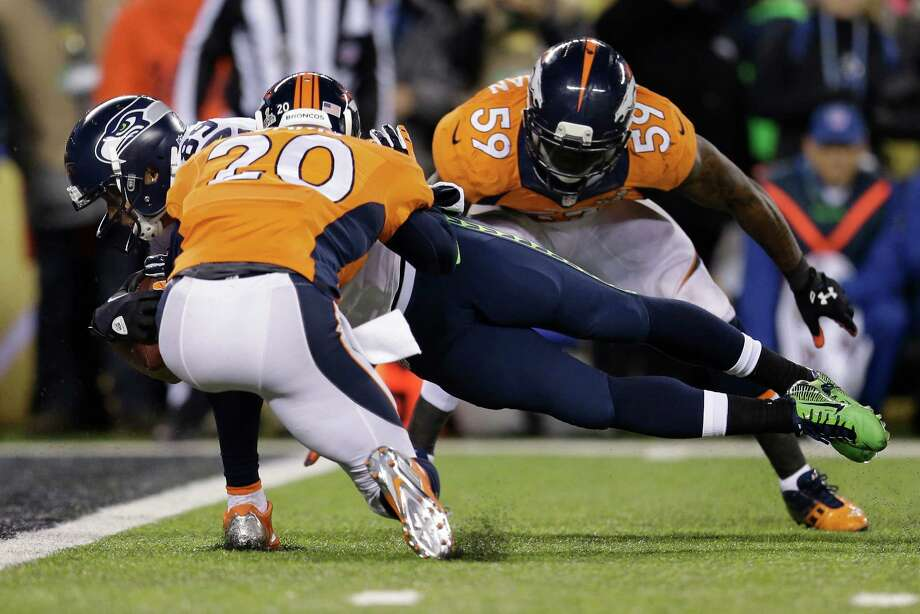 Seattle Seahawks' Doug Baldwin dives between Denver Broncos' Mike Adams, left, and Danny Trevathan for a touchdown during the second half of the NFL Super Bowl XLVIII football game Sunday, Feb. 2, 2014, in East Rutherford, N.J. Photo: Julio Cortez, AP / AP
