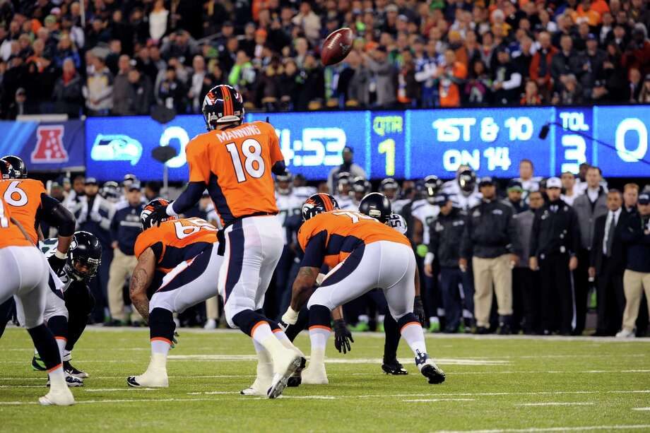 Denver Broncos quarterback Peyton Manning turns as the snap sails past him and into the end zone on the first play from scrimmage, resulting in a safety that gave the Seattle Seahawks a 2-0 lead in the NFL Super Bowl XLVIII football game at MetLife Stadium in East Rutherford, N.J., Feb. 2, 2014. (Barton Silverman/The New York Times) ORG XMIT: XNYT97 Photo: BARTON SILVERMAN / NYTNS