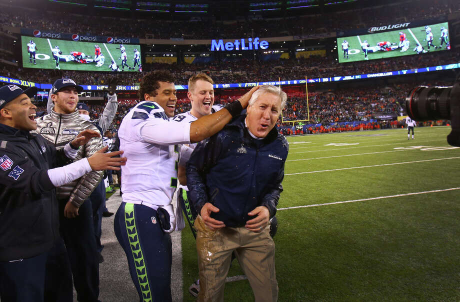 Russell Wilson celebrates with Pete Carroll after Gatorade was duped on the coach in the final minutes of the Super Bowl on Sunday, February 2, 2014 at MetLife Stadium in New Jersey. The Seahawks dominated the Denver Broncos 42-8. Photo: By JOSHUA TRUJILLO, SEATTLEPI.COM / SEATTLEPI.COM