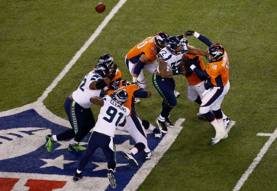 Quarterback Peyton Manning #18 of the Broncos throws a pass under pressure. Photo: Jeff Zelevansky, Getty Images