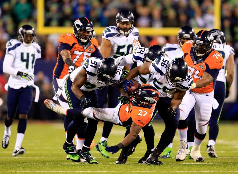 Running back Knowshon Moreno #27 of the Broncos is tackled by defensive end Chris Clemons #91, defensive end Cliff Avril #56 and middle linebacker Bobby Wagner #54 of the Seahawks. Photo: Rob Carr, Getty Images